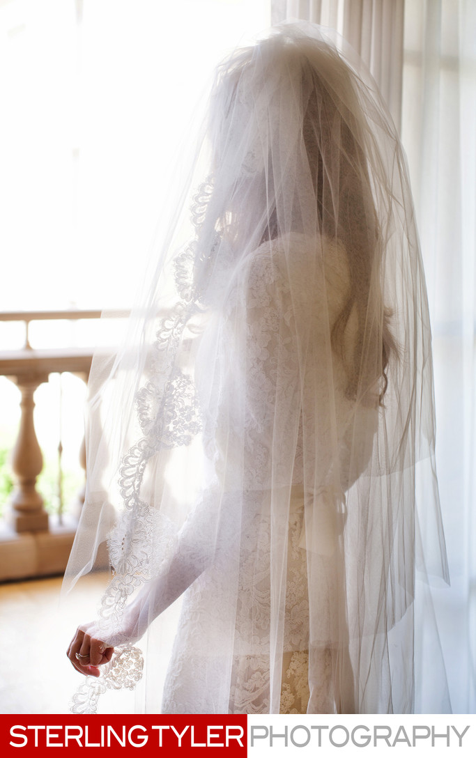 jewish bride with veil overlooking window