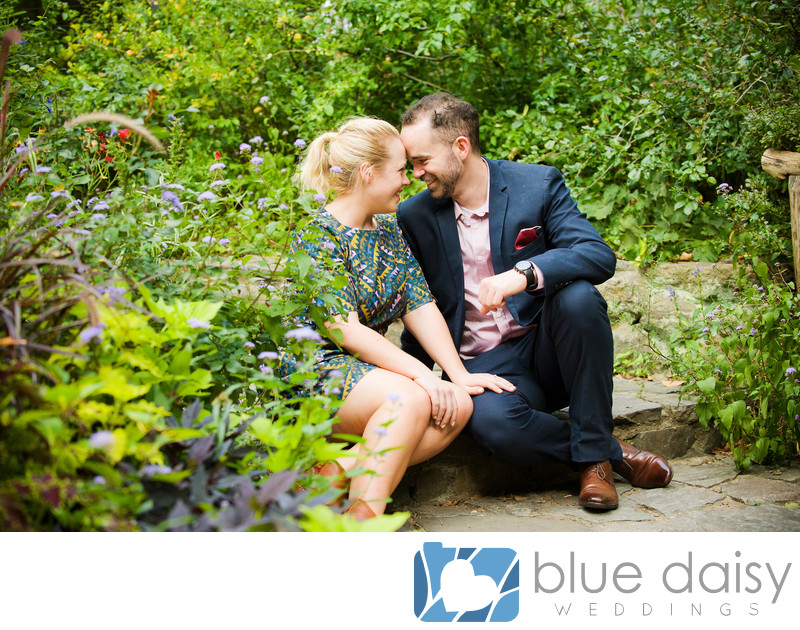Engaged couple sitting in summer Shakespeare Garden