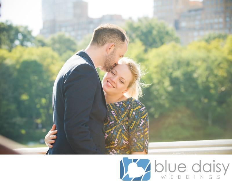 Newly engaged couple kiss on Bow Bridge in Central Park