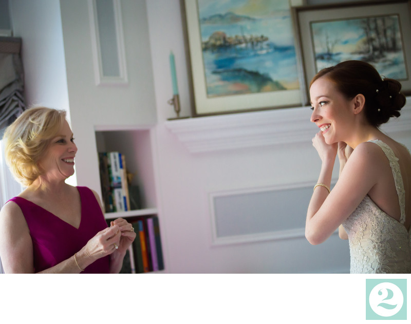 Bride Putting Earrings On and Laughing with Mother