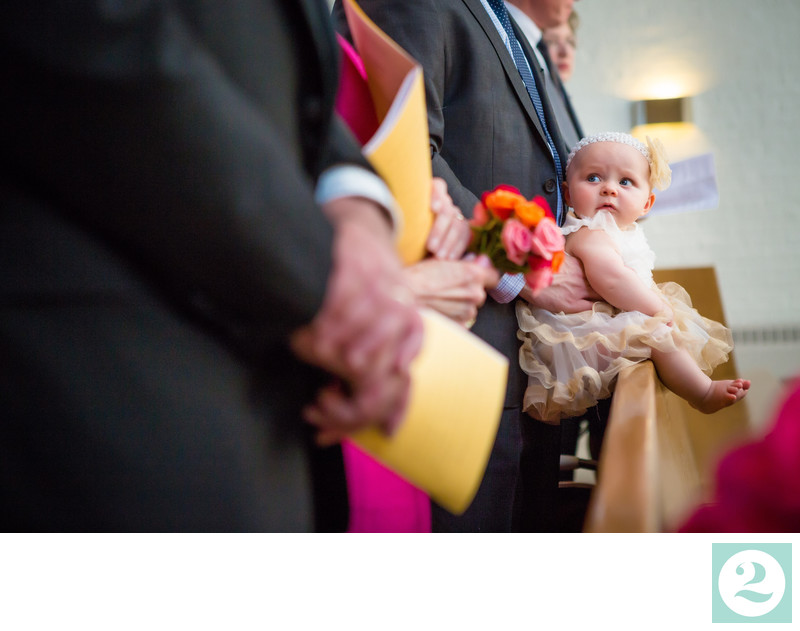 Baby Flower Girl Sits on Pew During Wedding