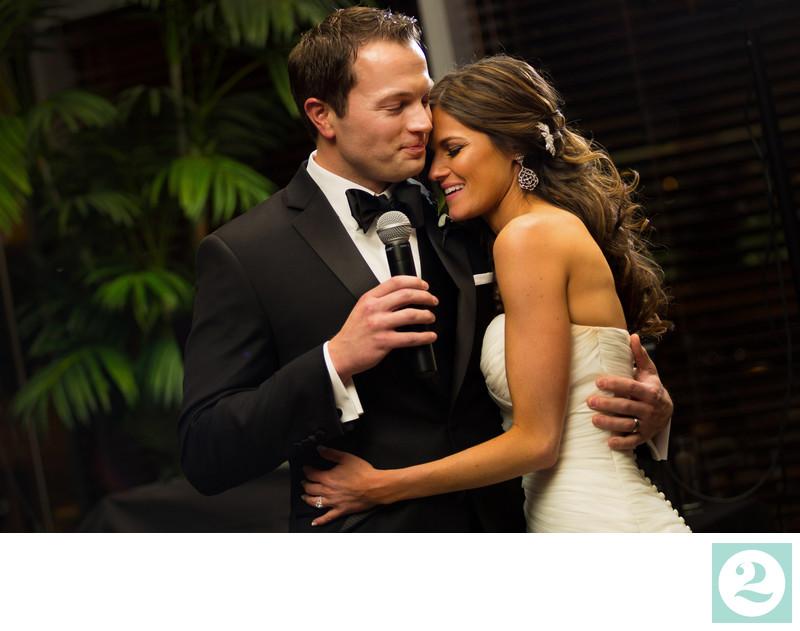 Bride and groom hug during wedding toast