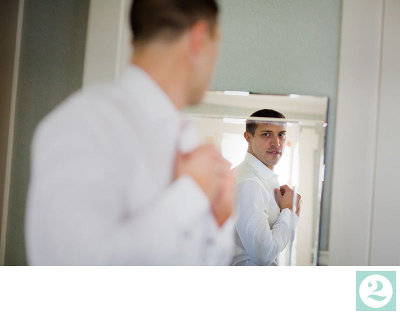 groom buttons his shirt in the mirror