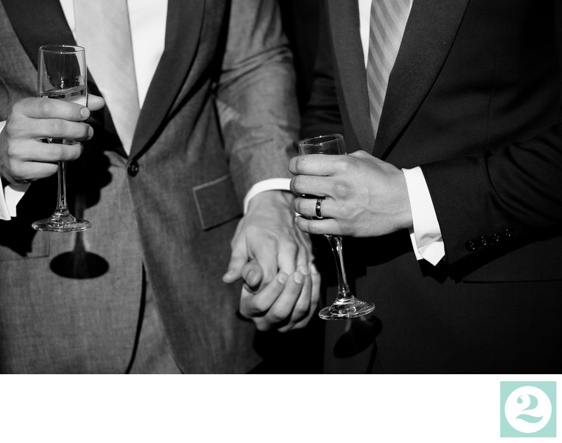 Two grooms holding hands during wedding toasts