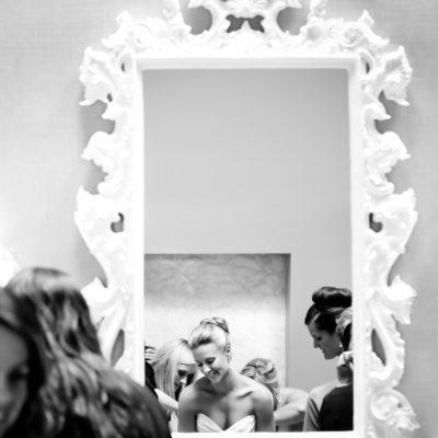 bride's friends help her into her dress