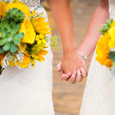 Two Brides Hold Hands with Yellow Flowers