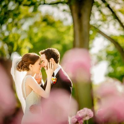 Perfect summer wedding portrait through purple flowers