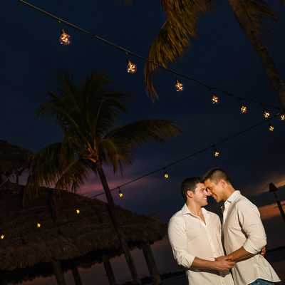Nighttime beach engagement shoot with palm trees