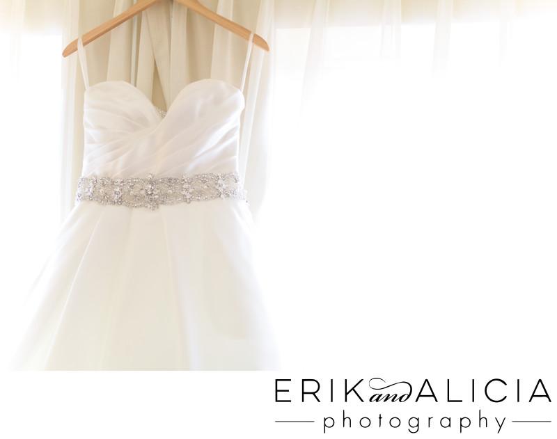 strapless wedding dress on hanger in window light