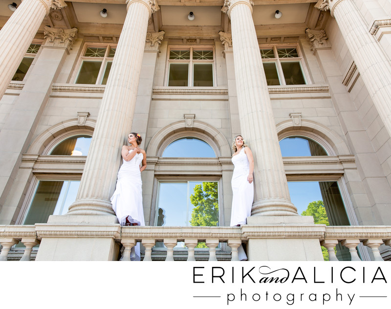two brides standing on balcony railing