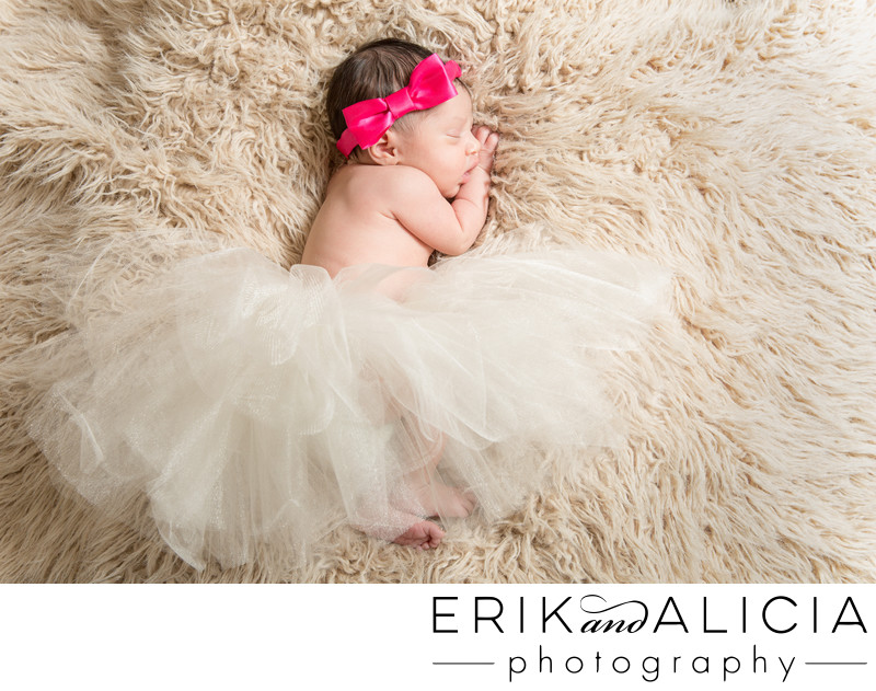newborn baby in a pink bow and tutu