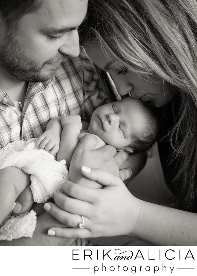 dad holds newborn boy mom kisses forehead