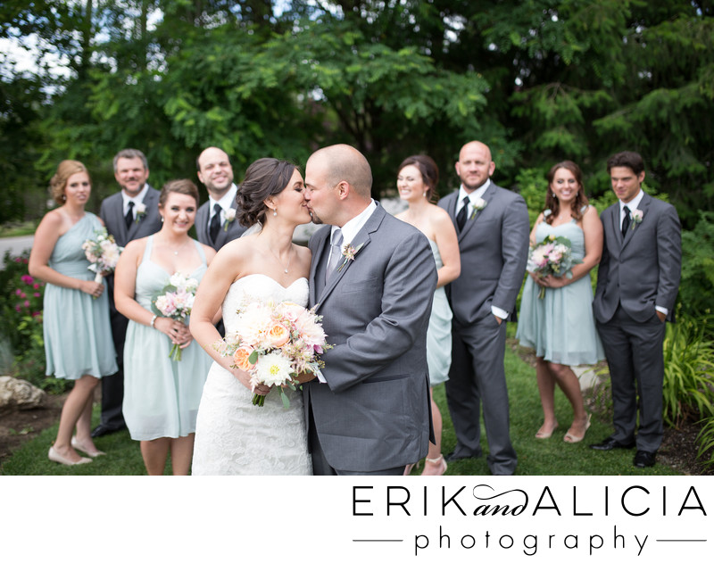 romantic wedding kiss with bridal party in background