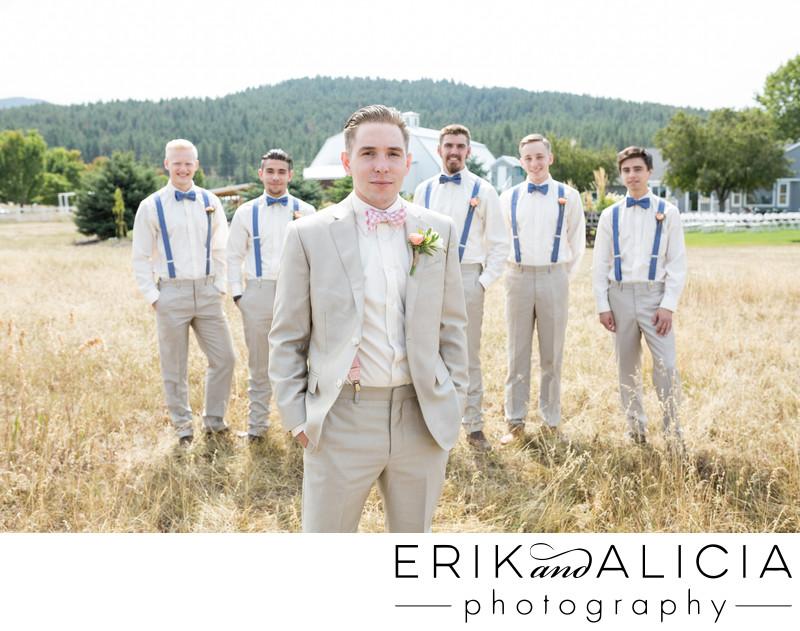 cool groom in field backed by groomsmen