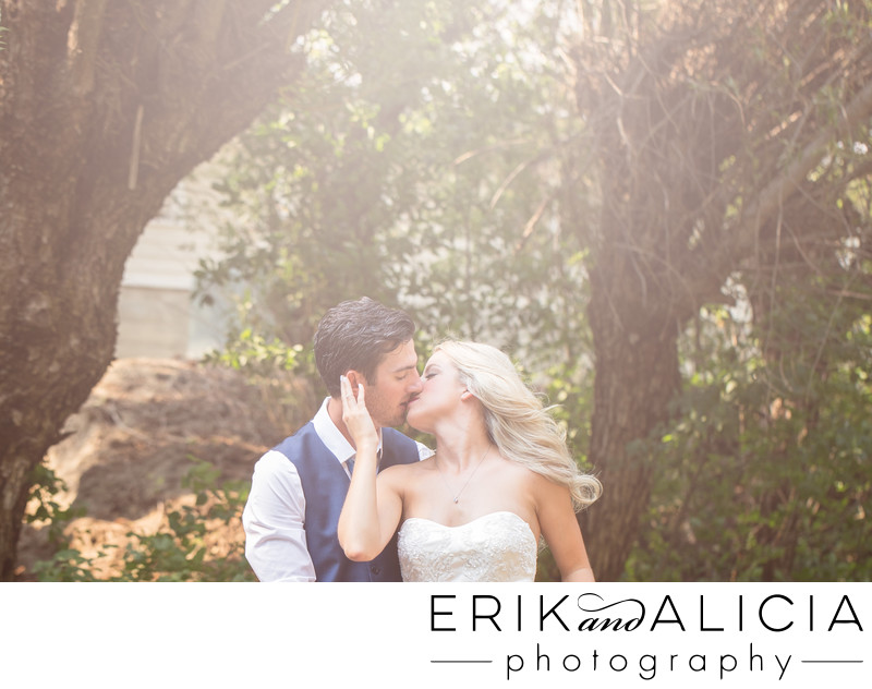 groom in blue vest romantic kiss with bride outside