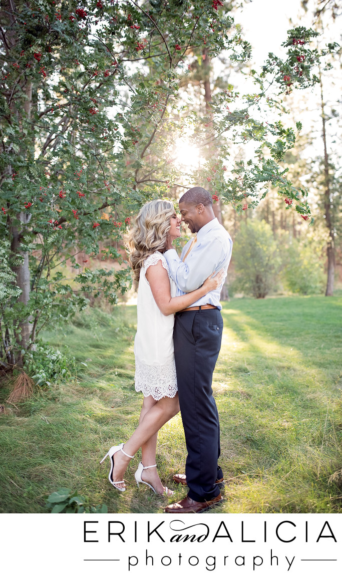 held kiss in a park of love engagement