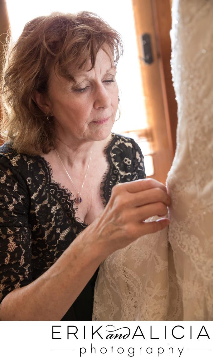 mom pins heirloom on brides dress