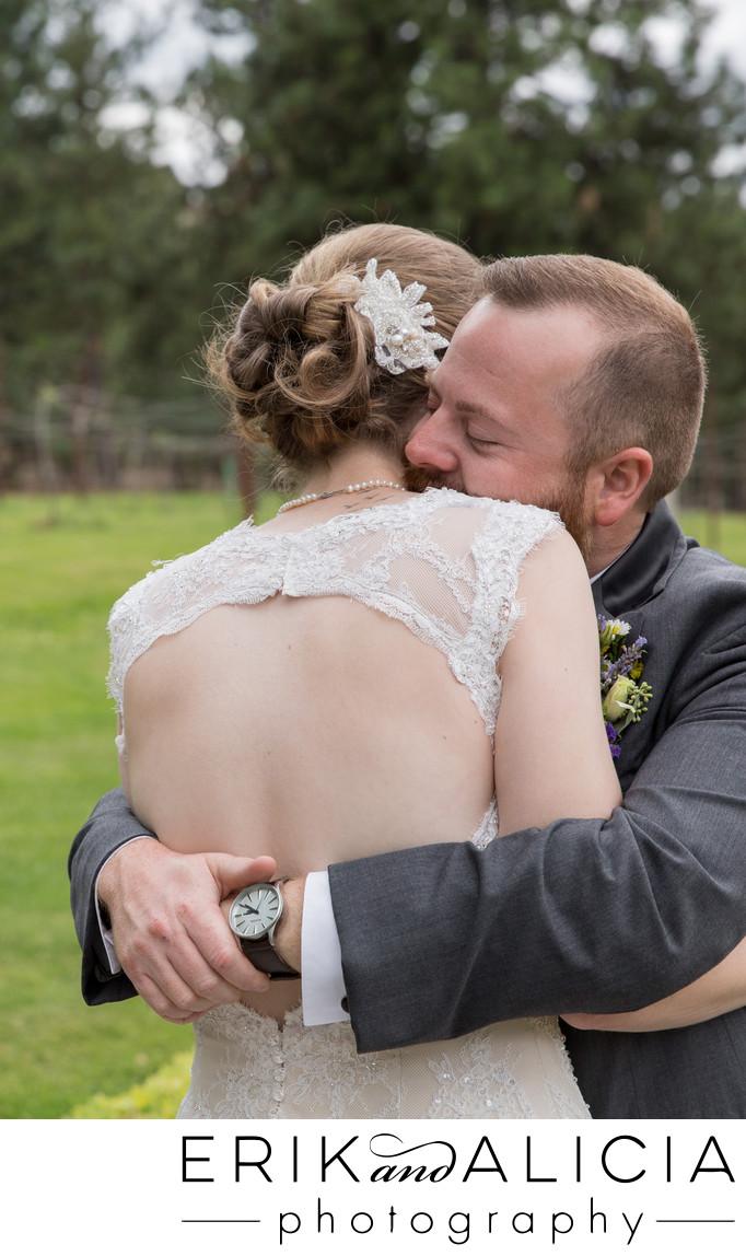 groom hugs bride in open back lace dress