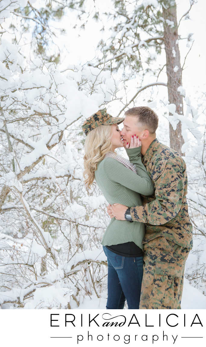 Great kiss in snowy woods wearing fatigues