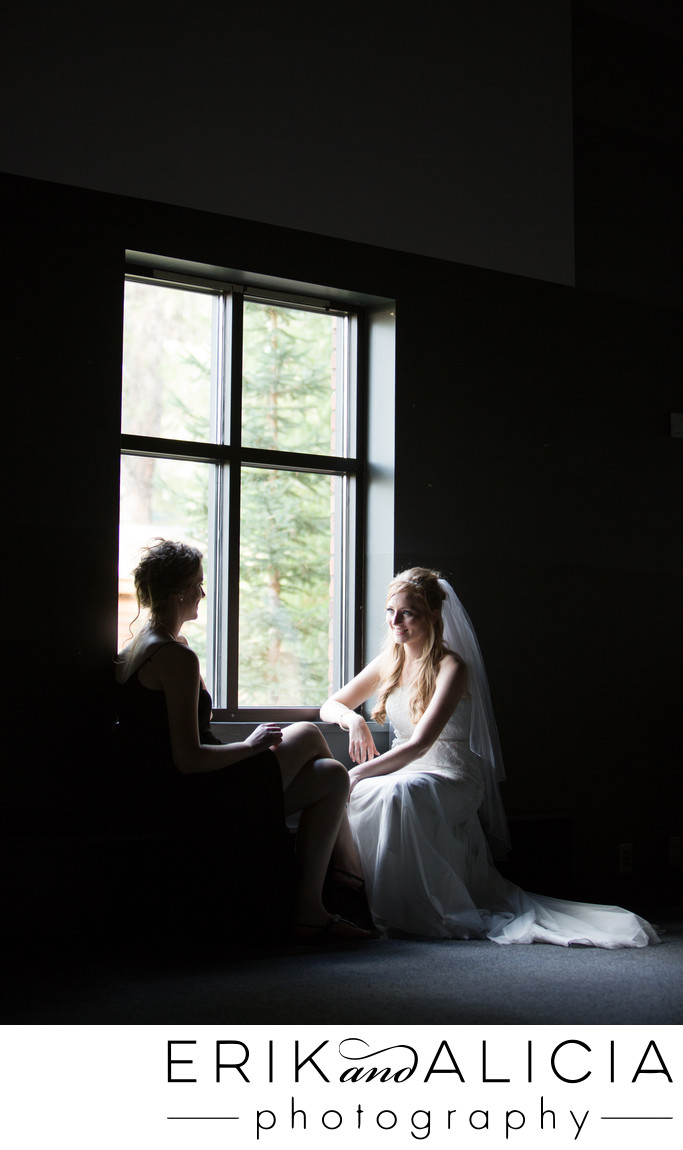 bride with maid of honor quiet moment lit window light