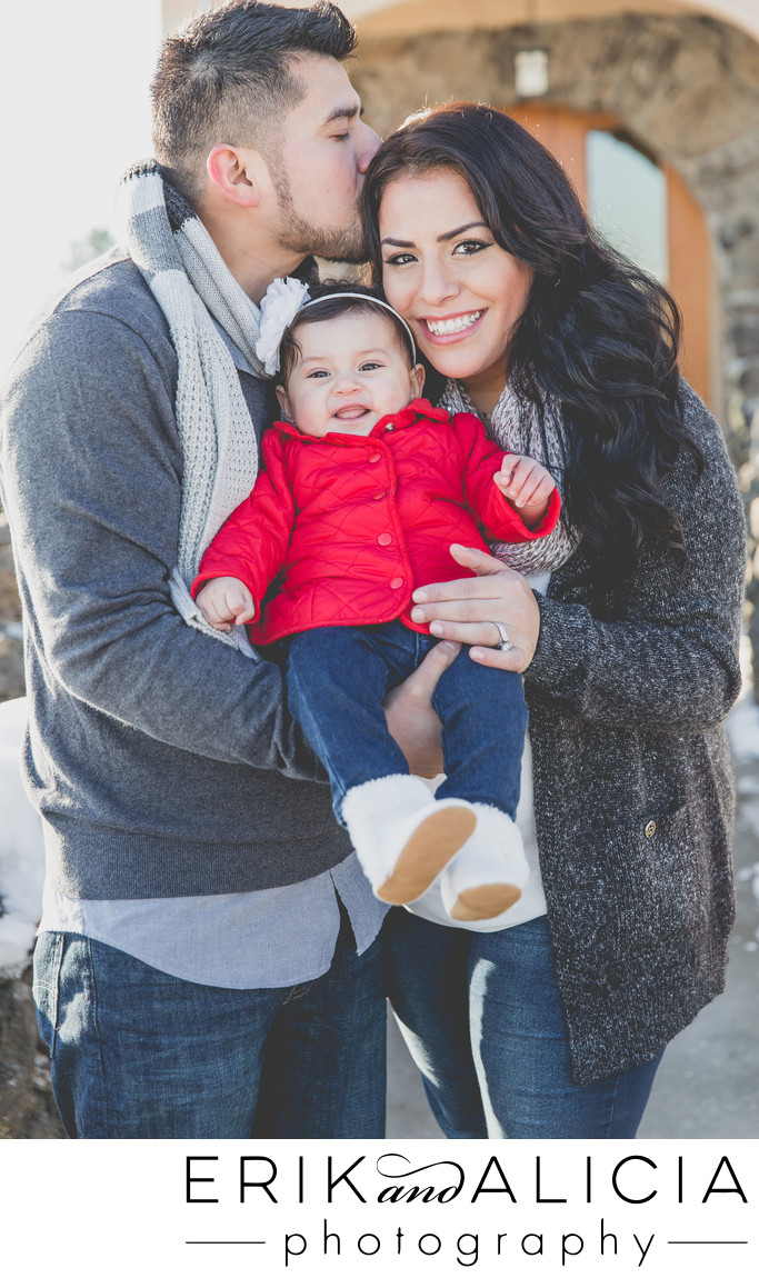baby girl in a red coat with mom and dad