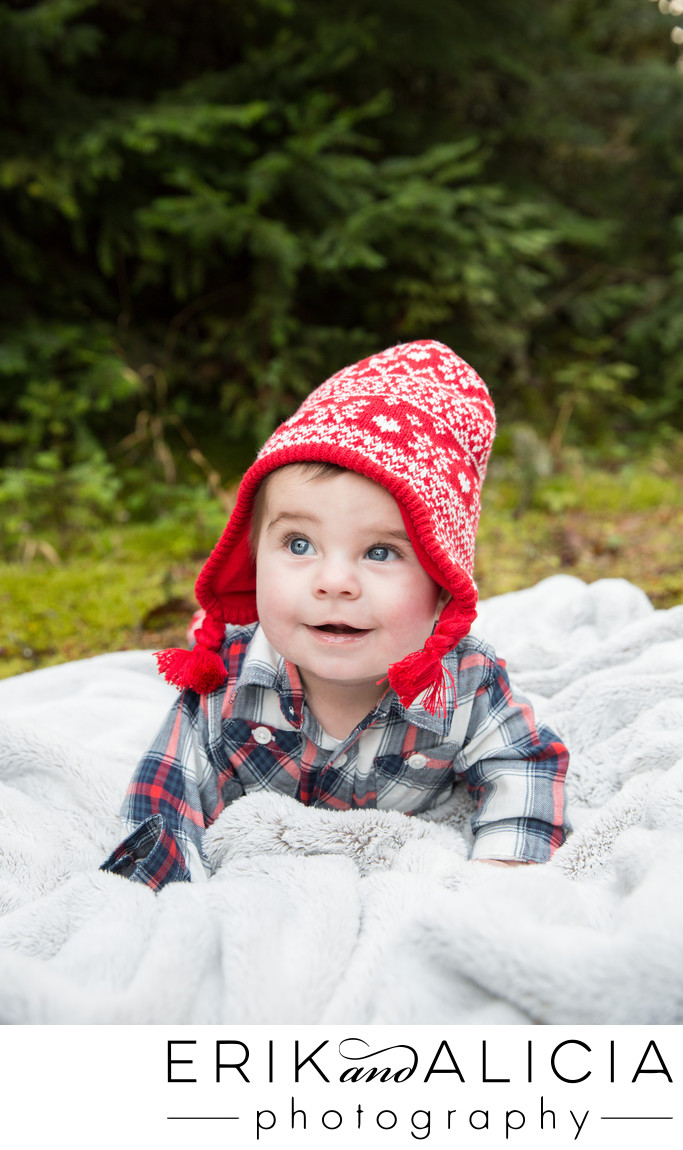 outside baby boy tummy time red hat plaid shirt