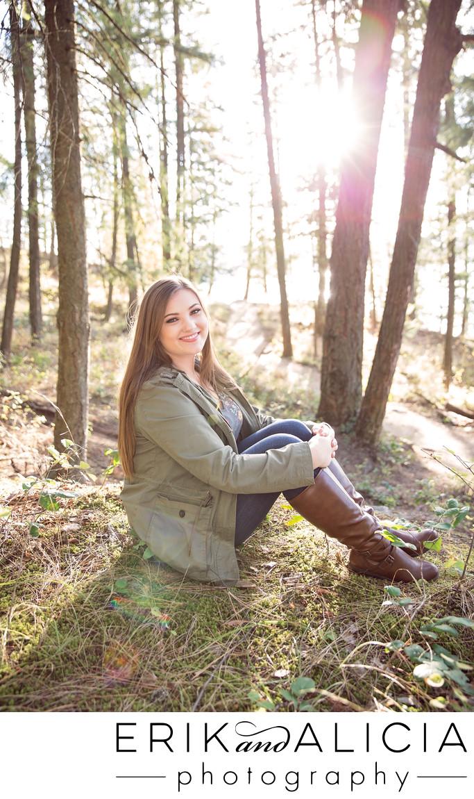 sun streaming through forest sitting hs senior girl