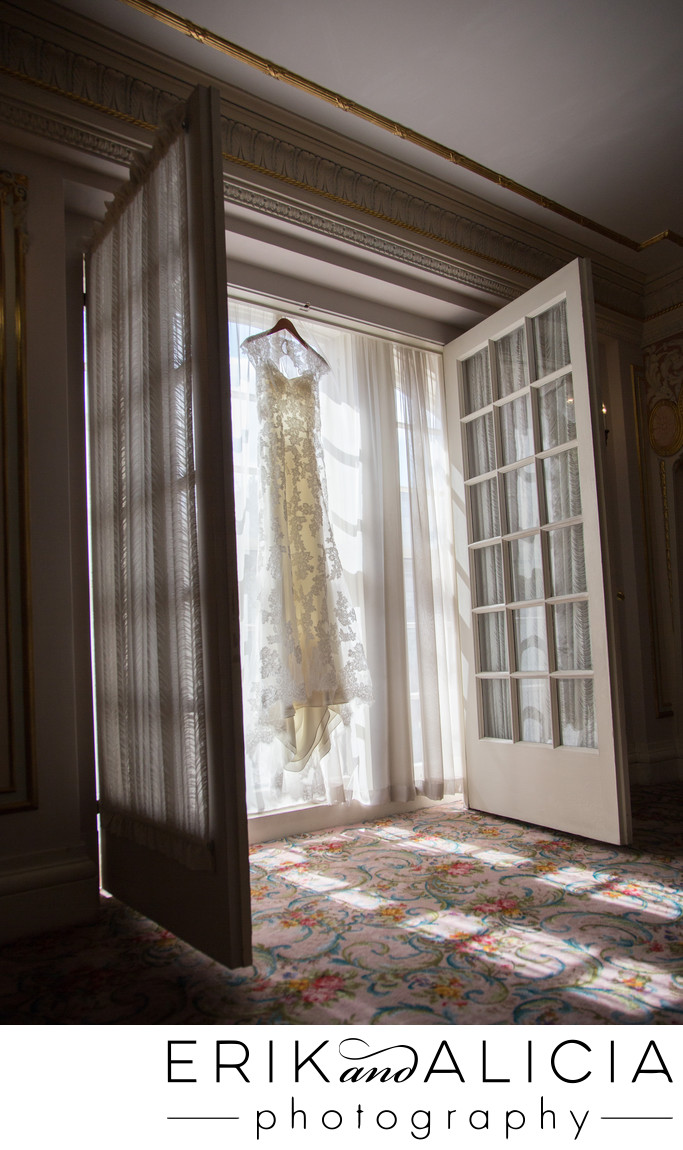 Wedding dress hanging in filtered light luxury hotel