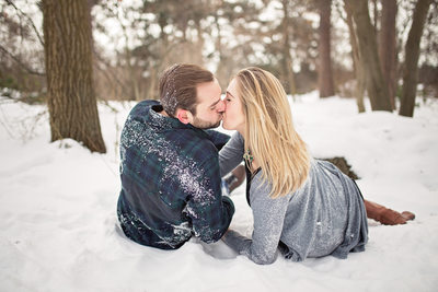 Couple laying on snow kissing