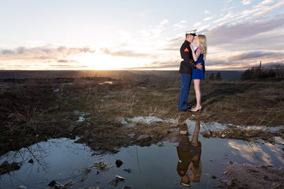 Dramatic sky with puddle reflection of military couple