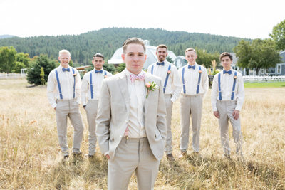 cool groom in field backed by groomsmen
