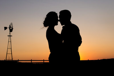 stunning silhouette kiss near windmill