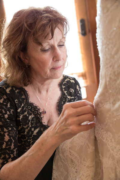 mom pins heirloom on brides dress