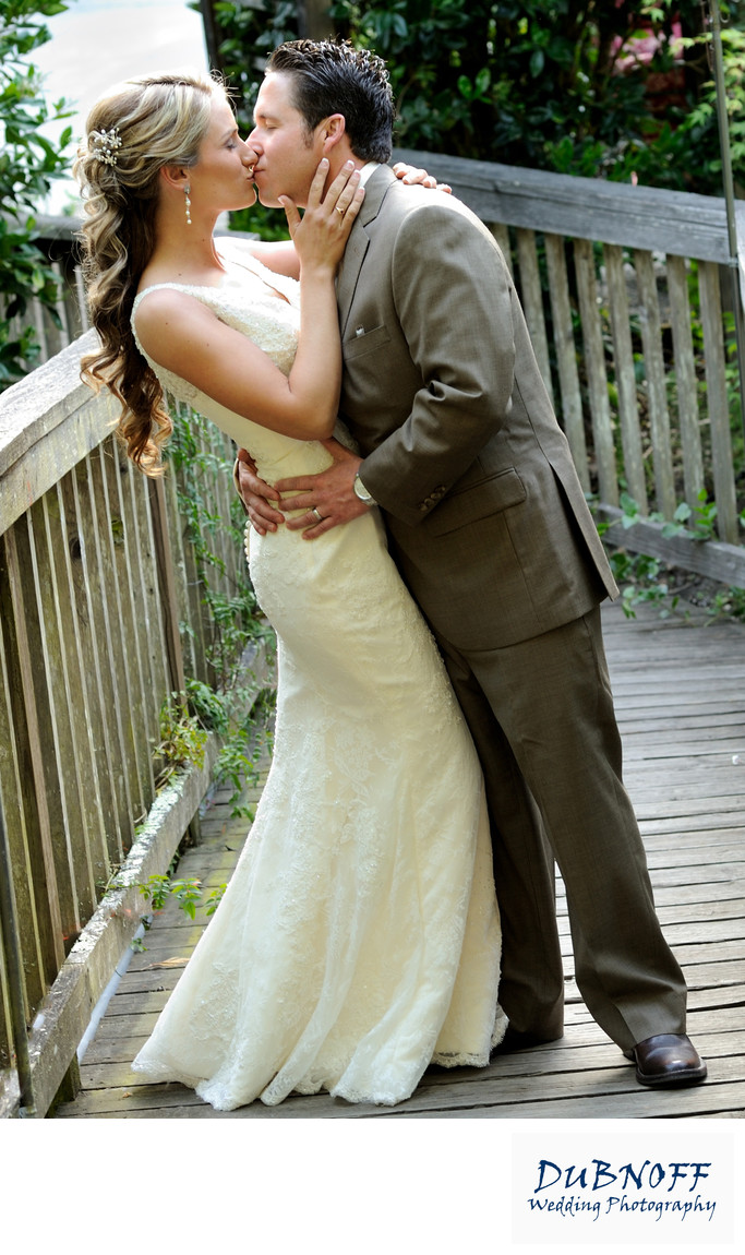 groom kissing bride on bridge
