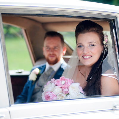 Wedding car & just married couple on their wedding day