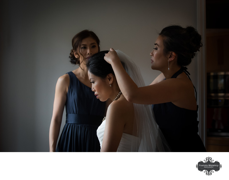 Bride having veil put on with bridesmaids by window