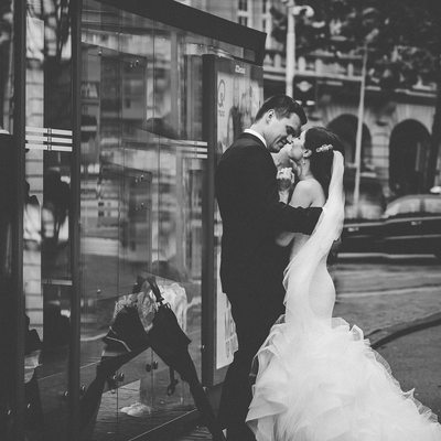 Journalistic Photo of Bride Stopping for Kiss on Street