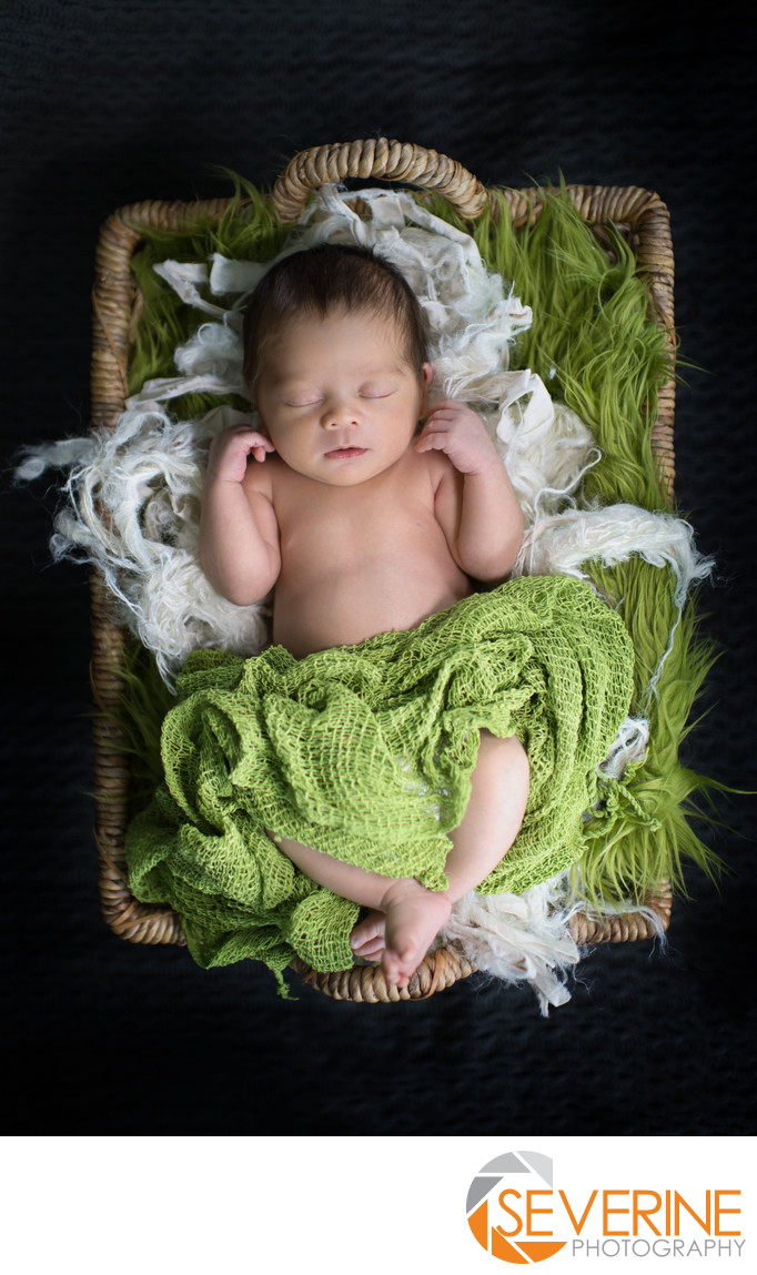 boy newborn with green blanket and natural basket