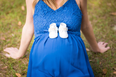 maternity photos with blue dress and white baby shoes