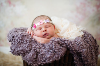 newborn girl with pink headset and purple blanket
