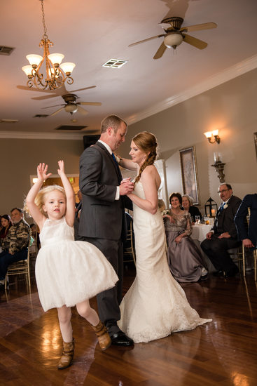 Flower girl dances with her mom and dad at first dance