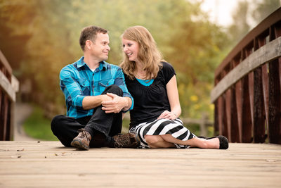 Engagement Photos of a Couple Sitting on a Bridge