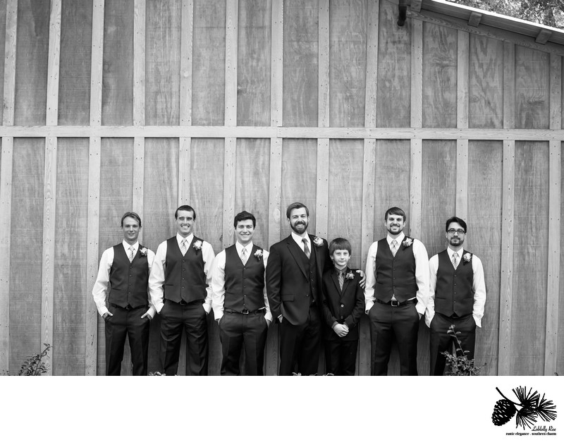 Groomsmen lined up on the side of the barn at Loblolly Rise