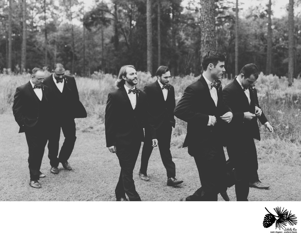 Groom walking with groomsmen while taking pictures before ceremony