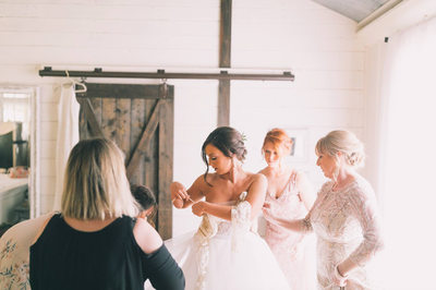 Bride puts on wedding dress in the cottage at Loblolly Rise