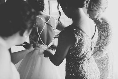 Bride getting ready with the help of her mom and bridesmaids