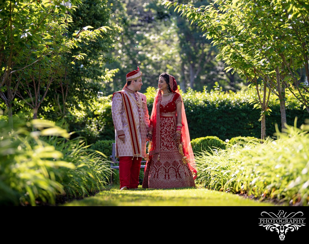 Indian Bride and Husband walking down a grassy aisle