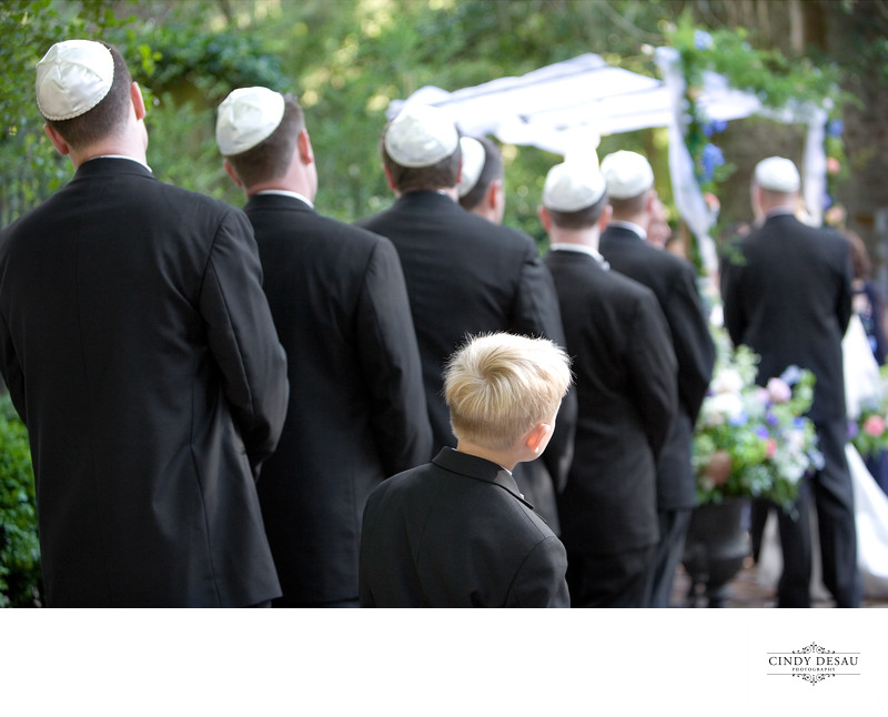 Candid Photo as Ring Bearer tries to Watch Jewish Wedding
