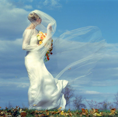 A Long Veil on a Windy Day Makes for a Dramatic Wedding Photo.