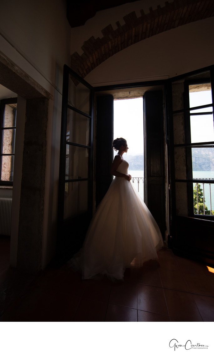 The thinking bride in a doorway in Malcesine Castle, IT
